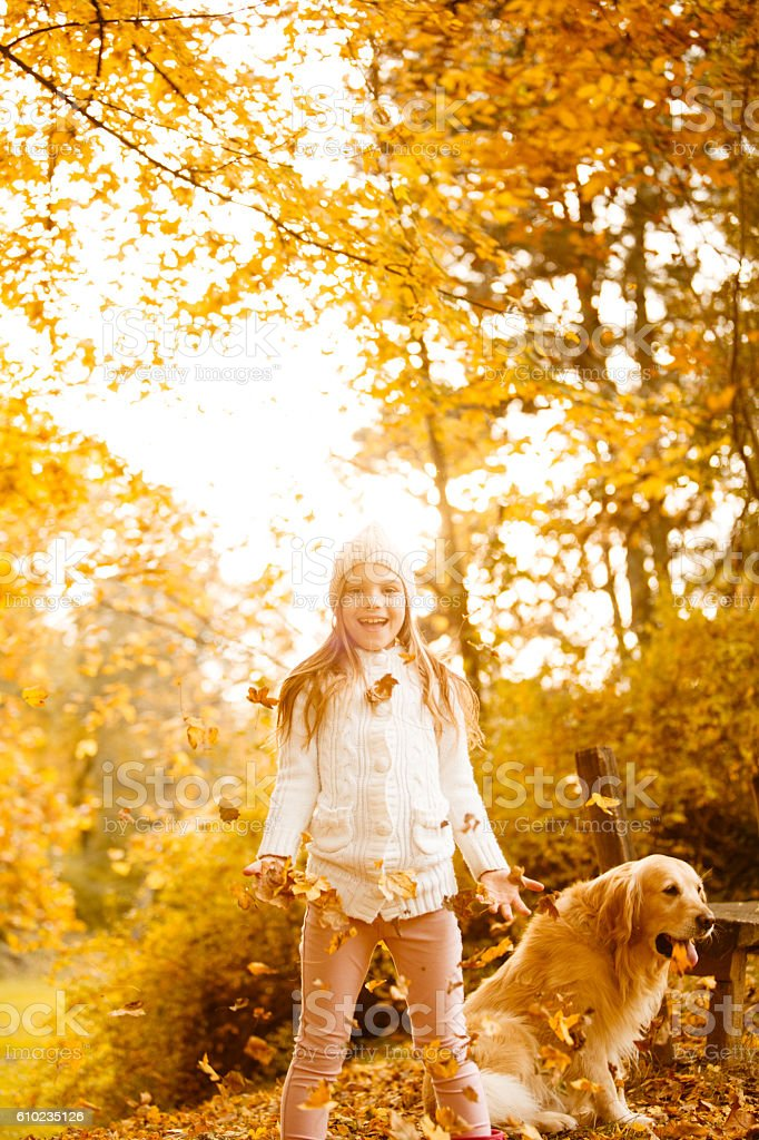 Girl playing with leaves in autumn park stock photo