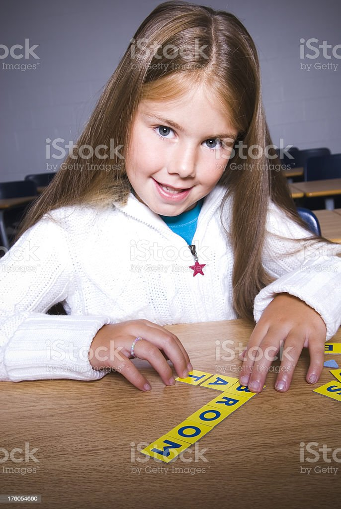 Girl playing with letters in the classroom - I royalty-free stock photo