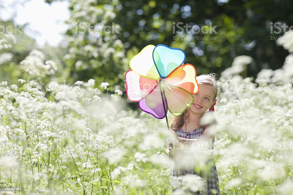 Girl playing with pinwheel in field of flowers stock photo