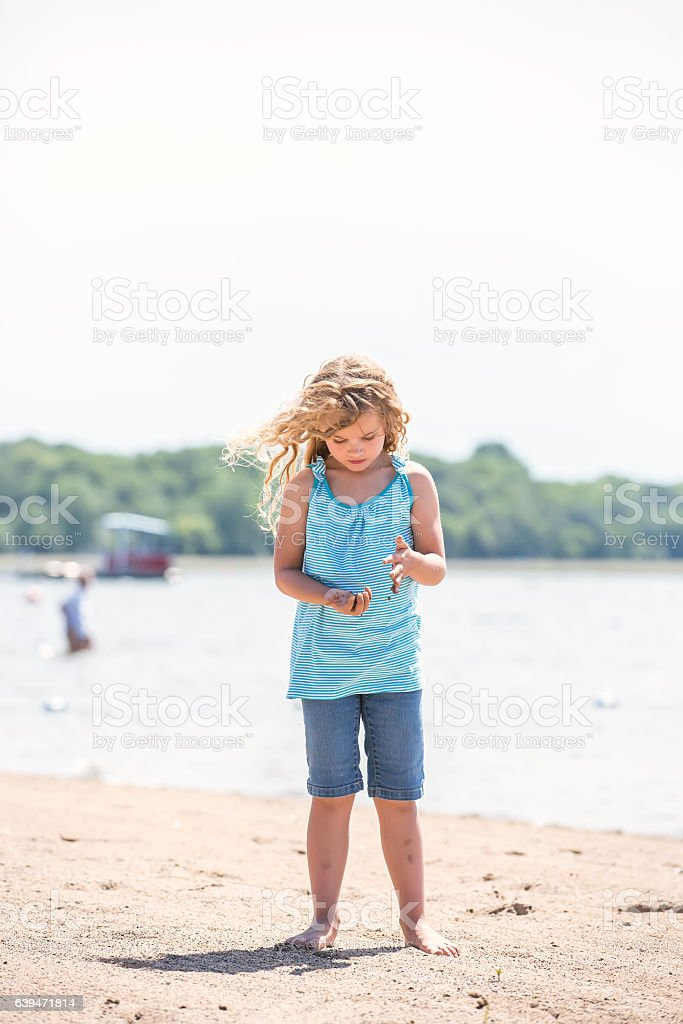 Girl Playing With Sand on Beach stock photo