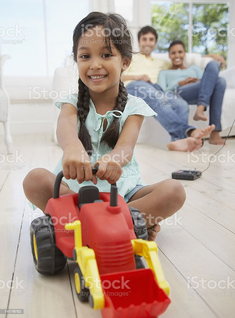Girl playing with toy dump truck with family in background royalty-free stock photo