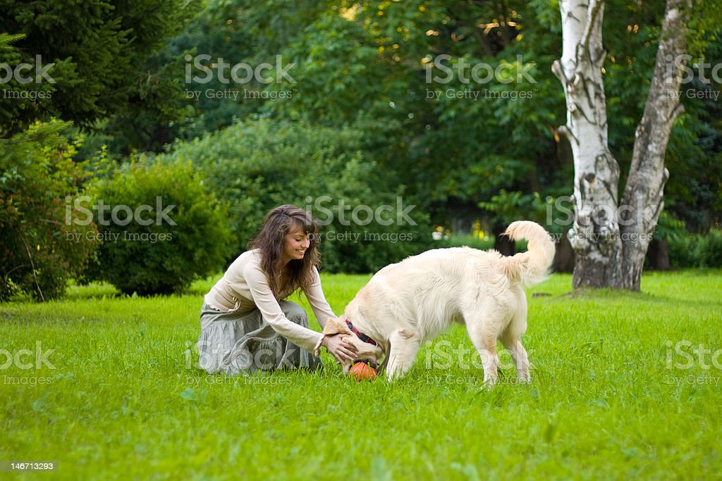Girl plays ball with a dog royalty-free stock photo