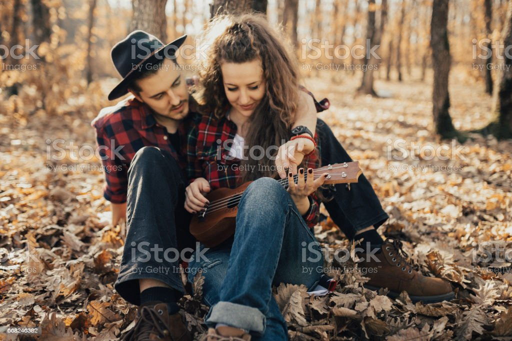 Girl plays the ukulele and sits in the arms of her boyfriend stock photo