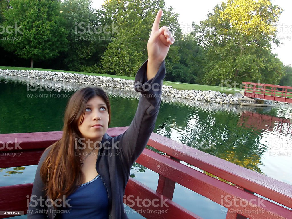 Girl pointing up to the sky stock photo
