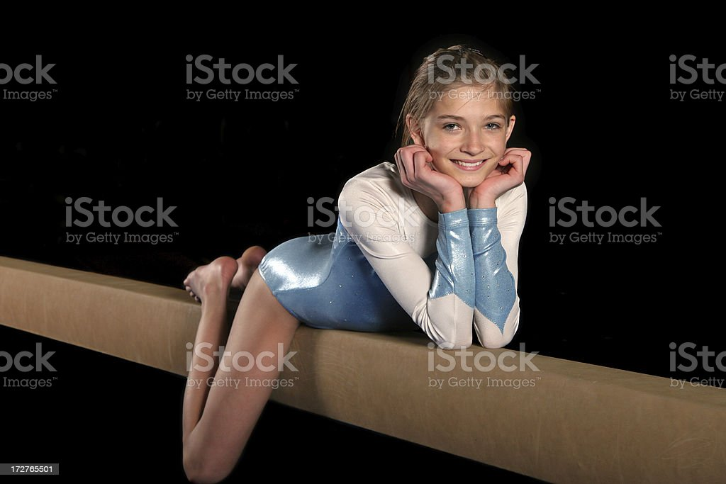 Girl poses on the balance beam stock photo