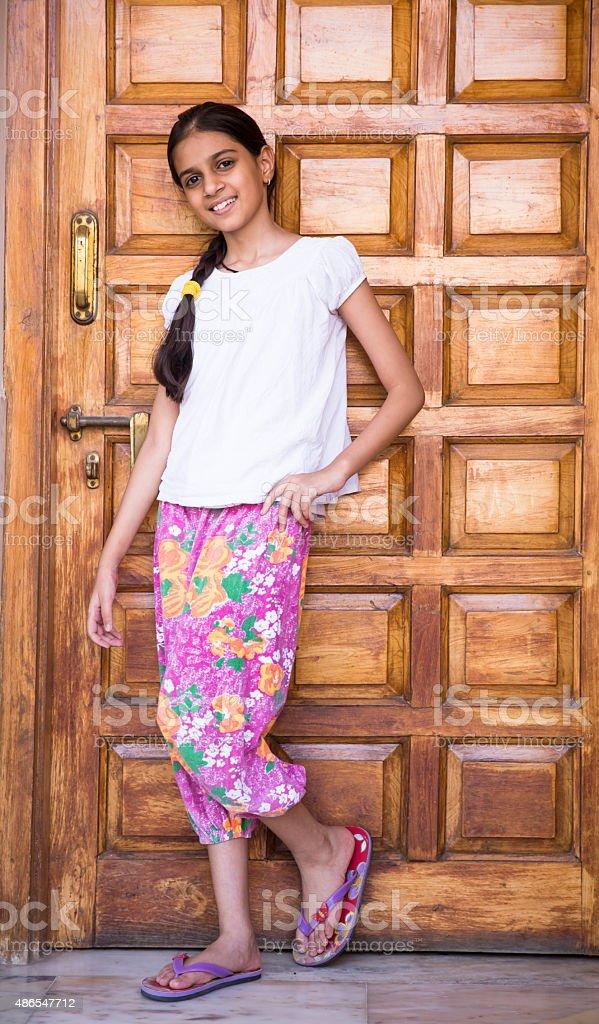 girl posing against a wooden door stock photo