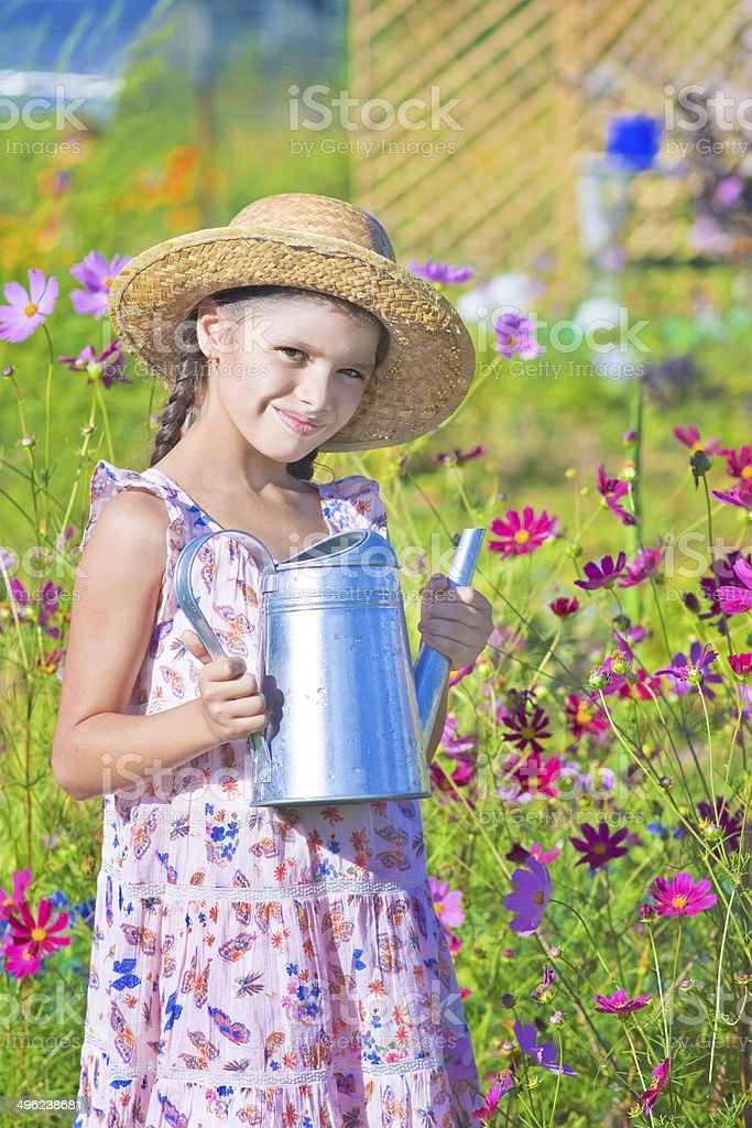 girl posing with metal watering can in summer royalty-free stock photo