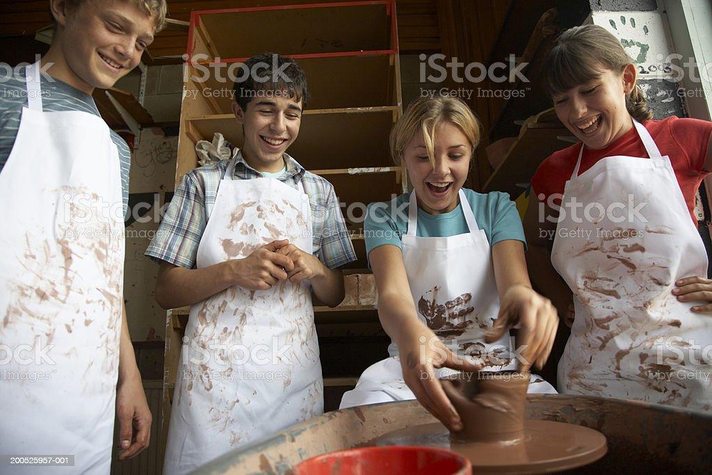 Girl (13-15) potting on wheel surrounded by classmates, smiling royalty-free stock photo