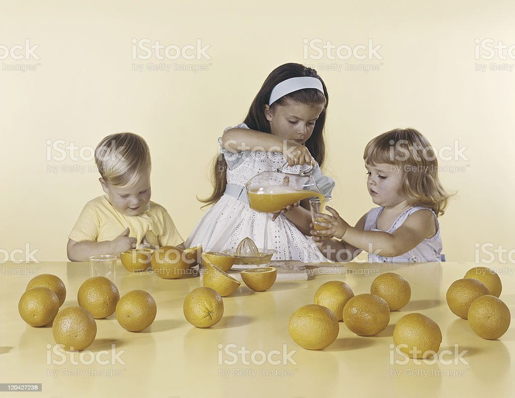 Girl pouring orange juice in glass royalty-free stock photo