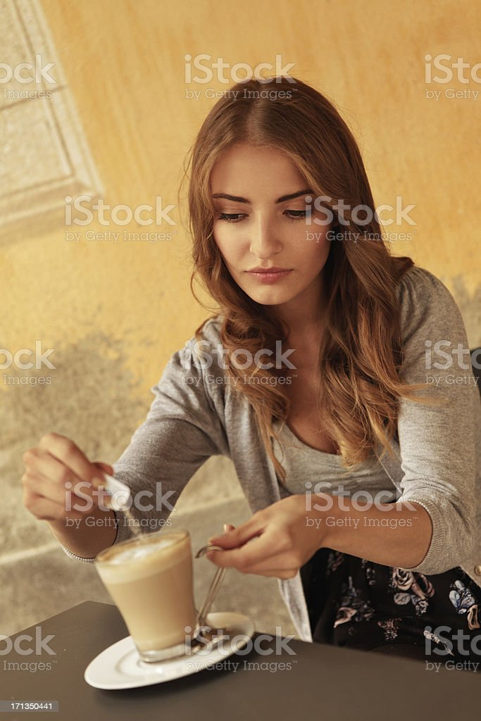 girl pouring sugar into latte stock photo