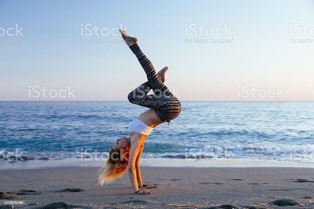 Girl practicing acrobatics yoga on beach during sunset stock photo