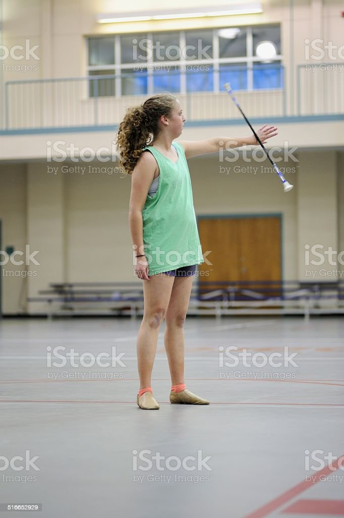 Girl practicing baton in gymnasium stock photo