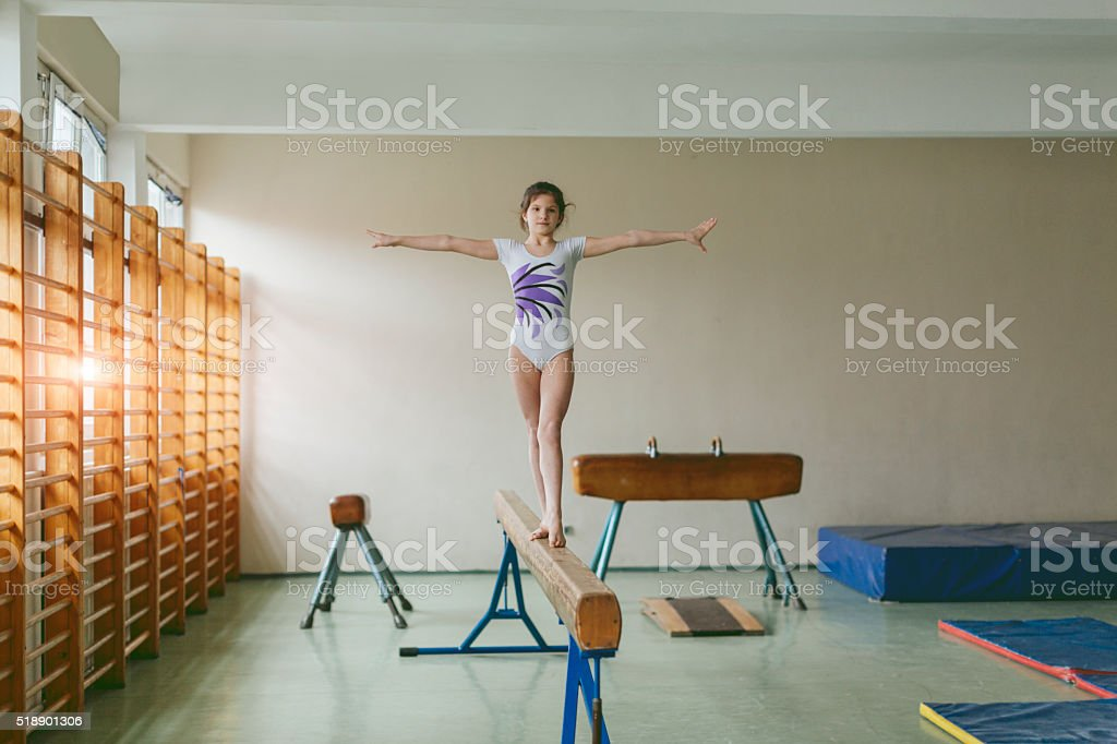 GIrl Practicing On Gymnastics Beam. stock photo