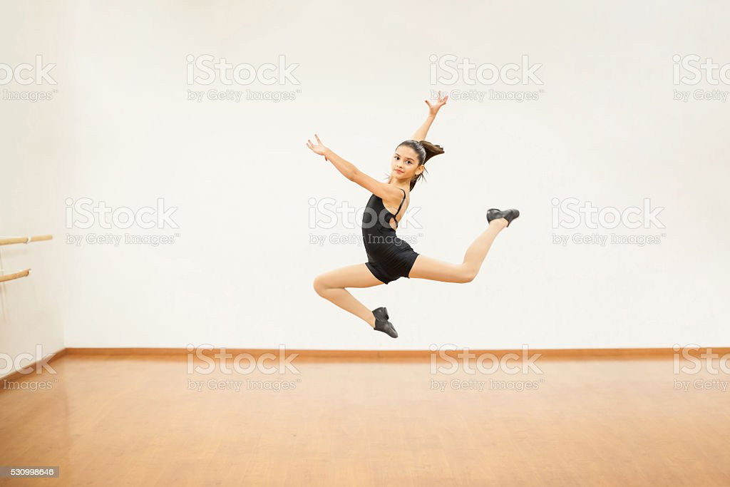 Girl practicing some jumps in dance class stock photo