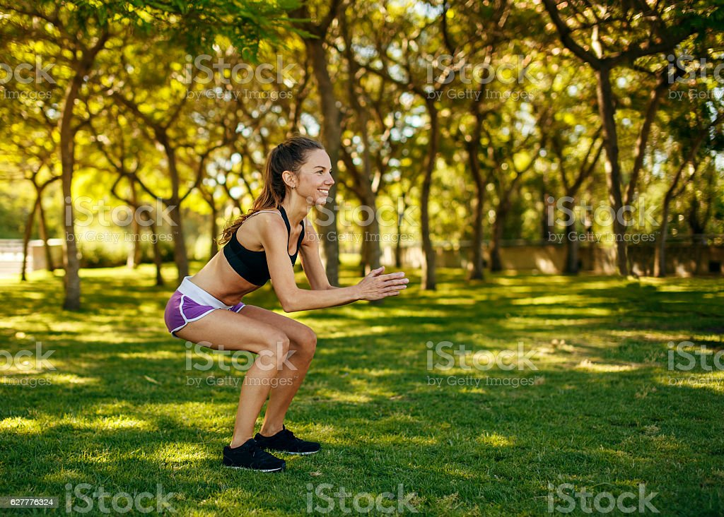 Girl practicing sport doing squat in the park stock photo
