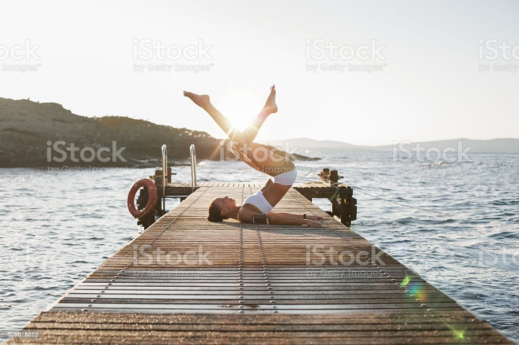 Girl practicing yoga at the quay stock photo