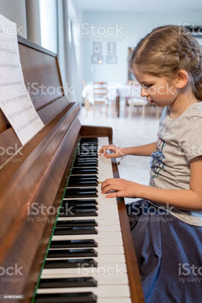 Girl practising playing the piano stock photo