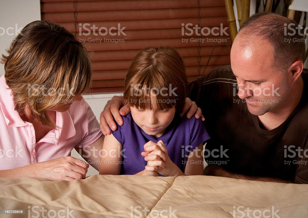 Girl praying with her mom and dad royalty-free stock photo