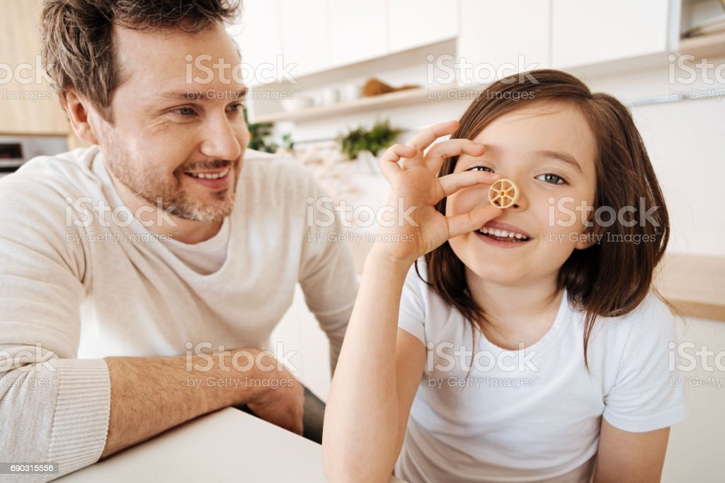 Girl pressing a piece of rotelle pasta to her nose stock photo