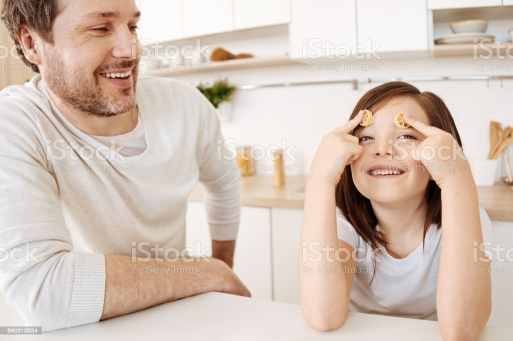 Girl pressing two pieces of rotelle pasta to her forehead stock photo