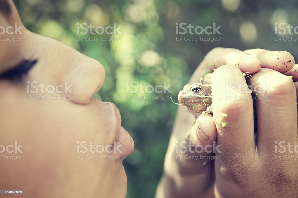 Girl Puckers Up to Kiss a Little Frog stock photo