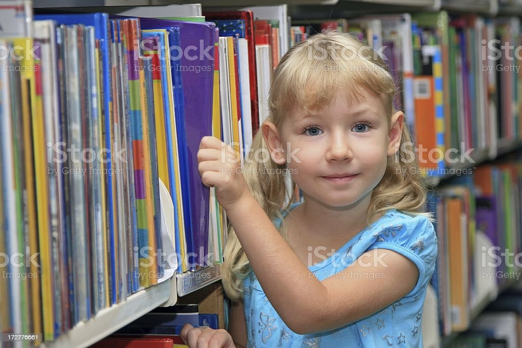 Girl pulling out a book from the shelves royalty-free stock photo
