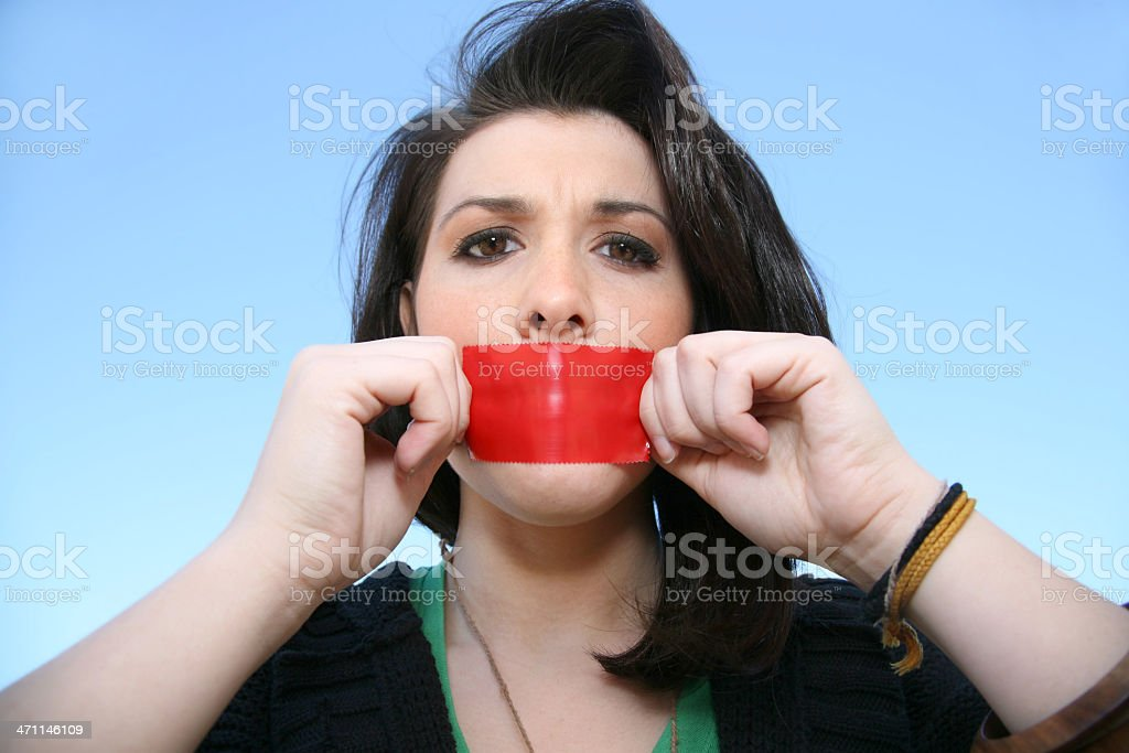 Girl pulling the tape off her mouth stock photo