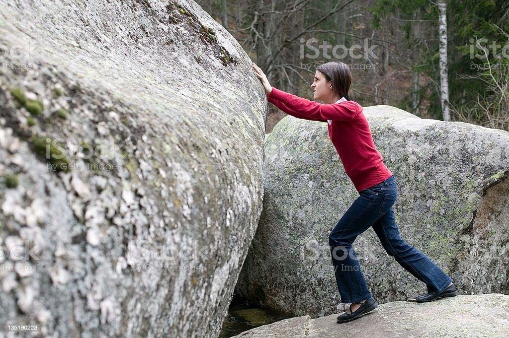 Girl pushing a stone royalty-free stock photo