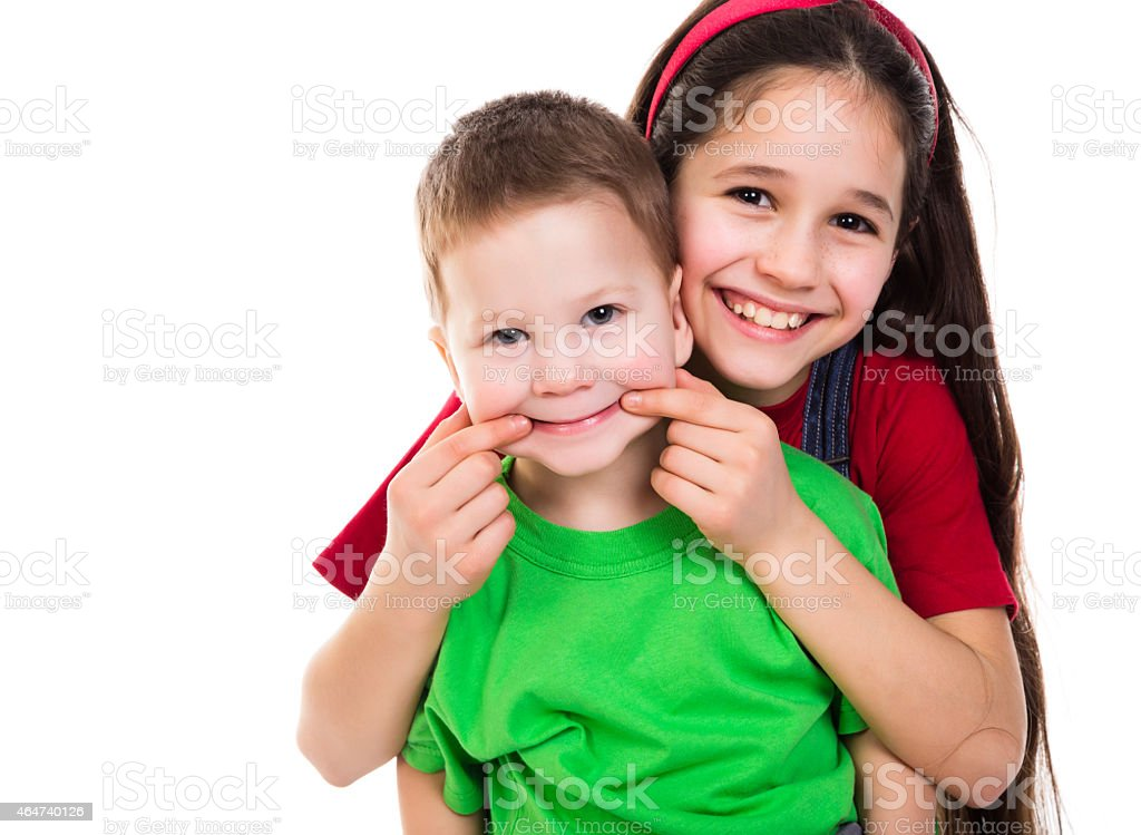 A girl pushing her little brother's face into a smile stock photo
