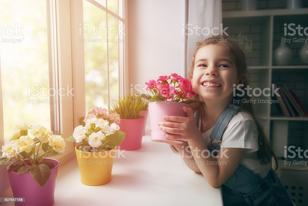girl puts flowers stock photo