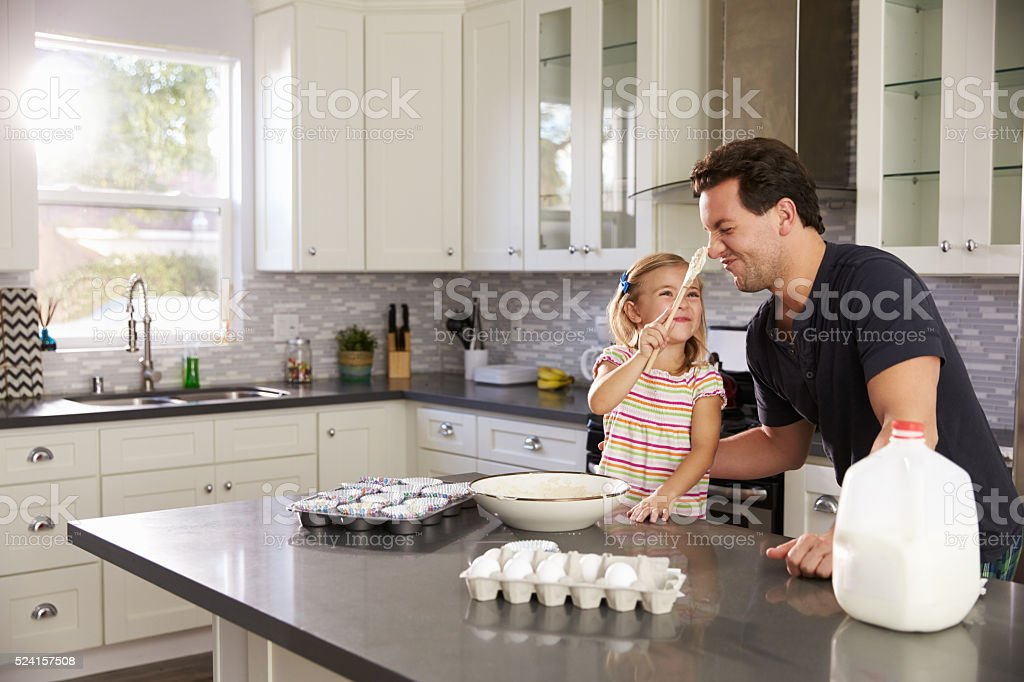 Girl putting cake mix on dad's nose while they stock photo