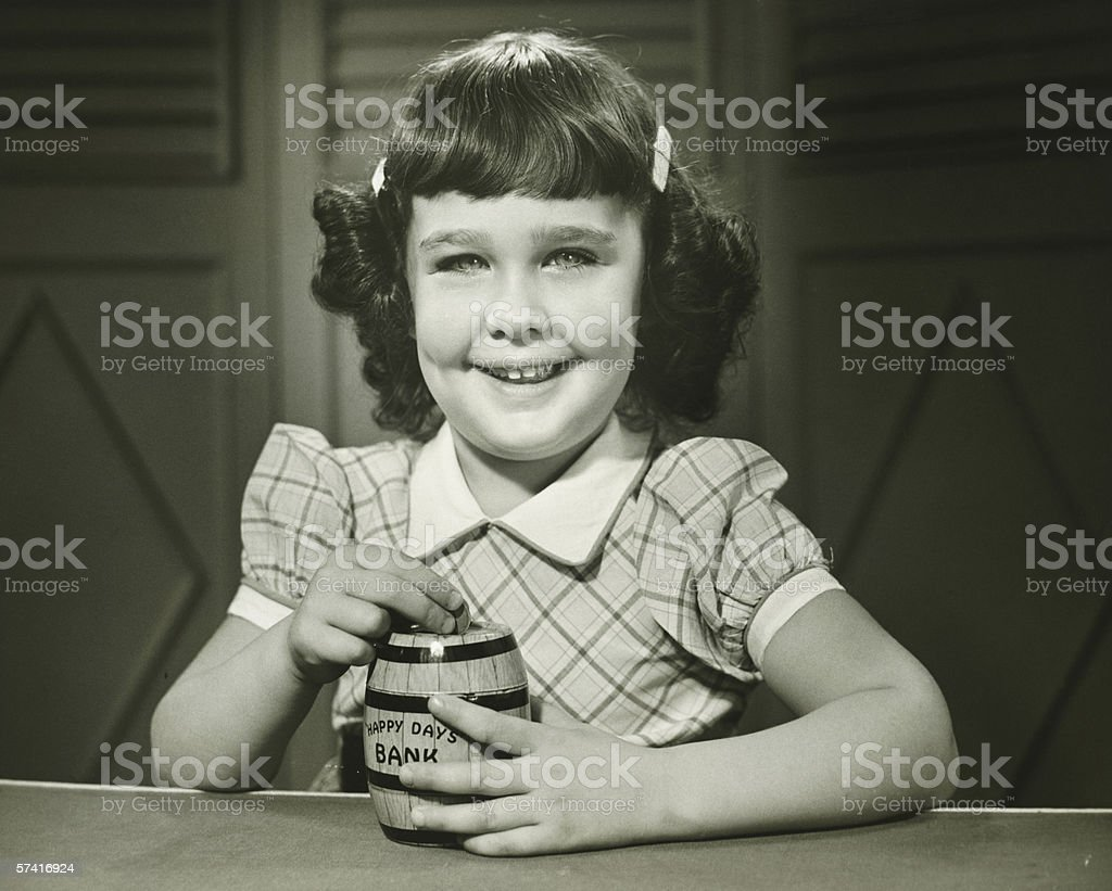 Girl (6-7) putting coin into money-box, (B&W), (Close-up), (Portrait) royalty-free stock photo