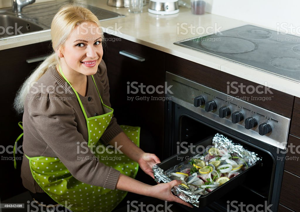 Girl putting  fish in oven stock photo