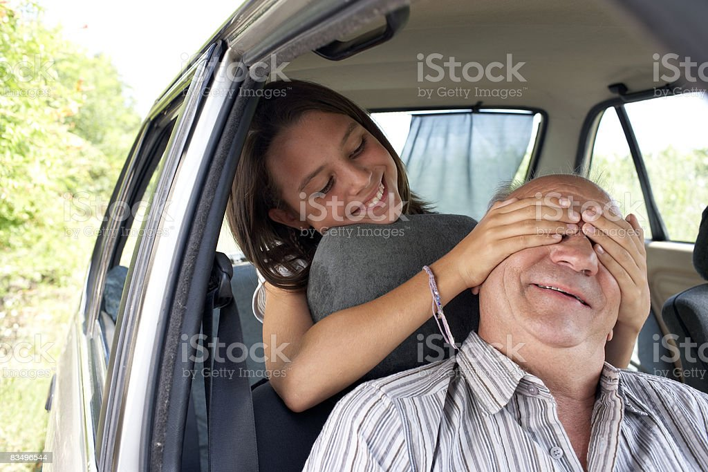 girl putting hands over grandfather's eyes royalty-free stock photo