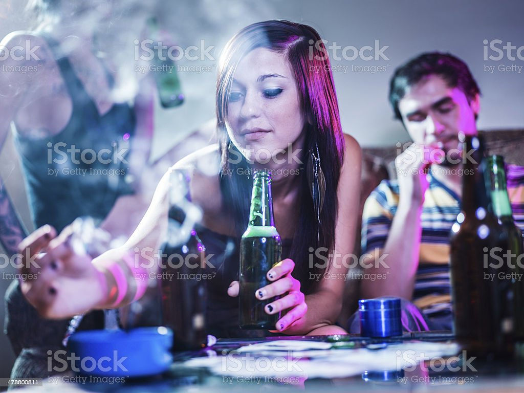 girl putting joint in ashtray at crazy party stock photo