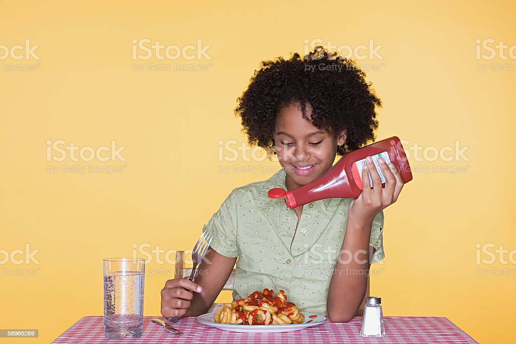 Girl putting ketchup on curly fries stock photo