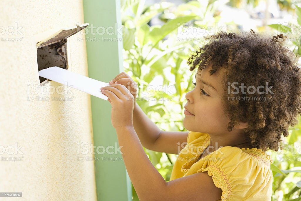 Girl putting mail through a mail slot in door stock photo