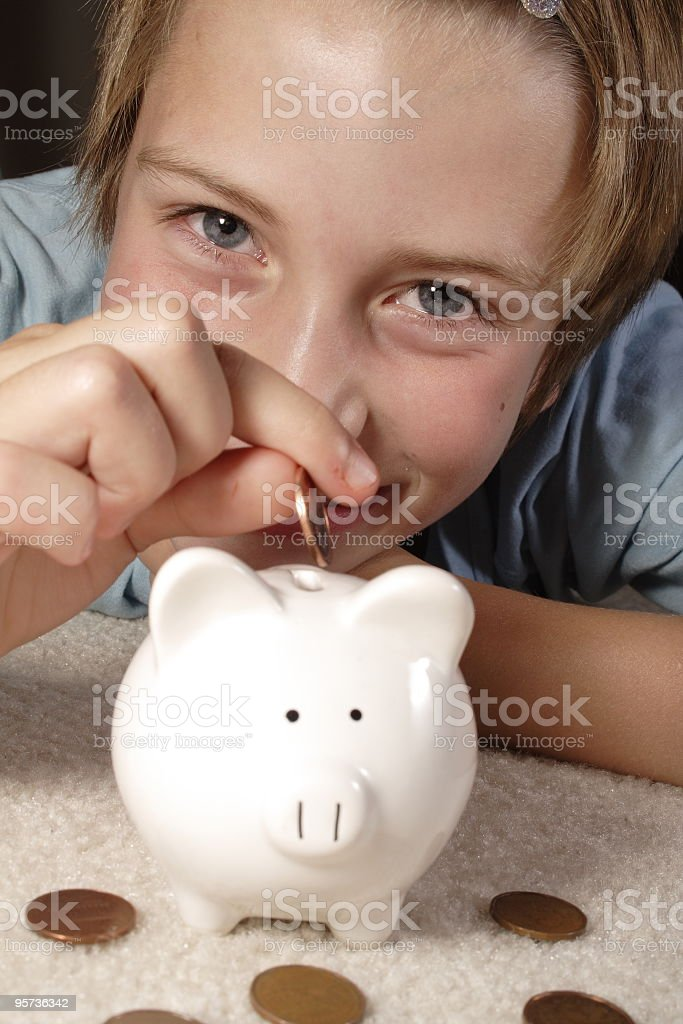 Girl putting money in a piggy bank royalty-free stock photo