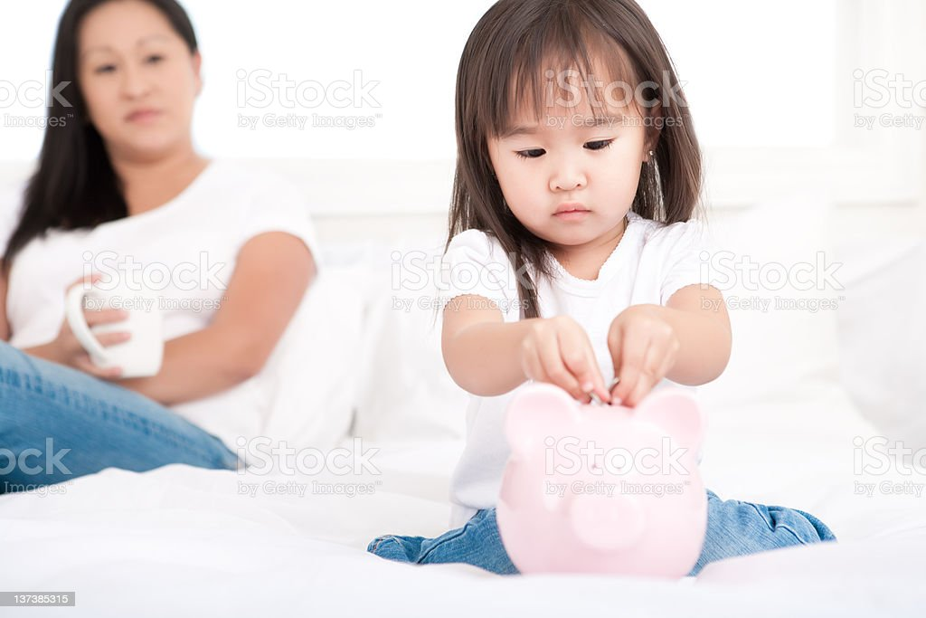 Girl putting money in piggy bank royalty-free stock photo