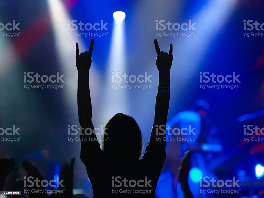 Silhouette of girl on rock concert raised up hands with rock-n-roll...
