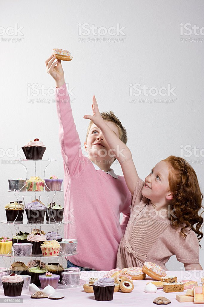 Girl reaching for doughnut that boy is holding stock photo