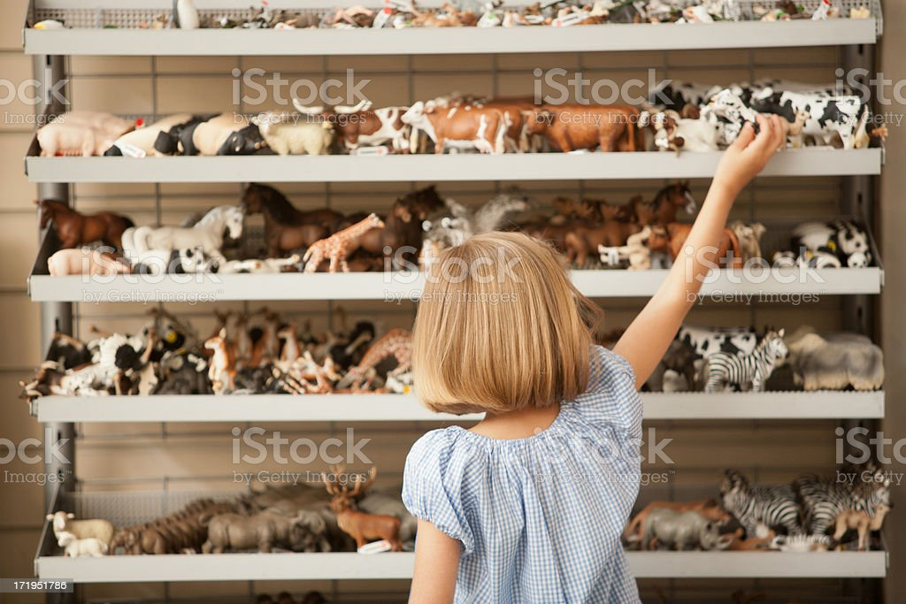 Girl reaching for plastic cow in toy store royalty-free stock photo