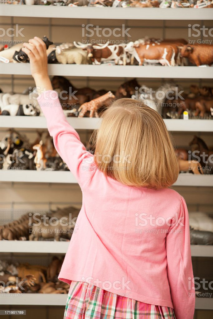 Girl reaching for plastic pig in toy store stock photo
