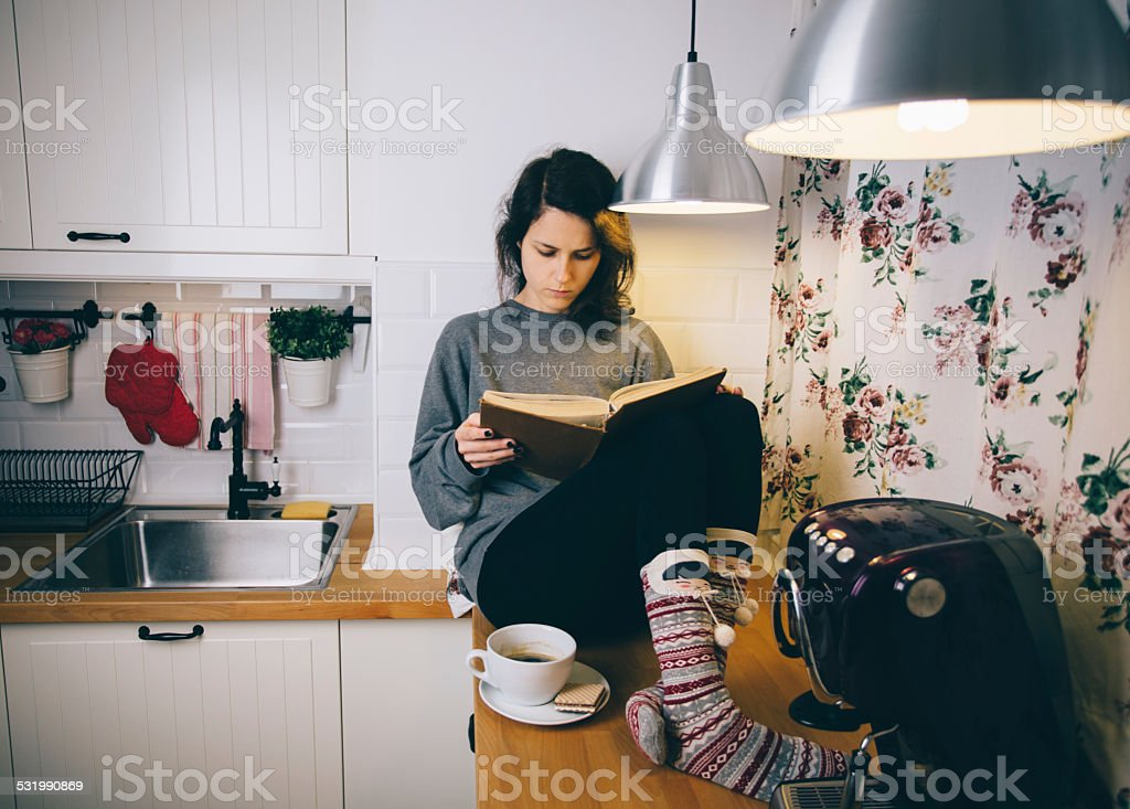 Girl reading a book at home stock photo