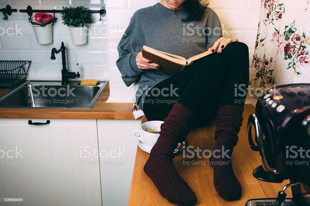 Girl reading a book at the kitchen stock photo