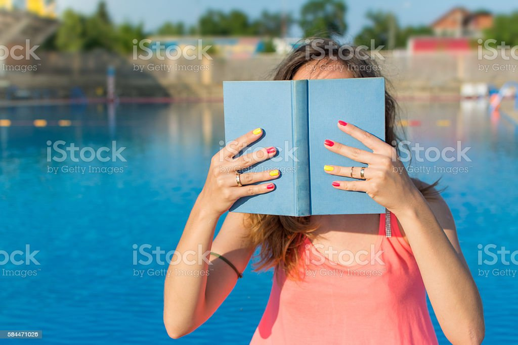 Girl reading a book by the pool. stock photo