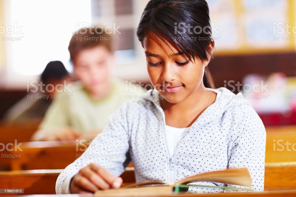 Girl reading a book in classroom royalty-free stock photo