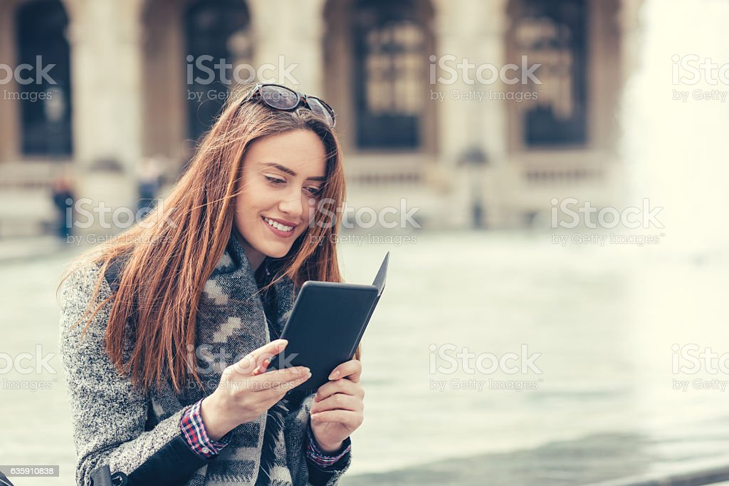 Girl reading a book in the city stock photo