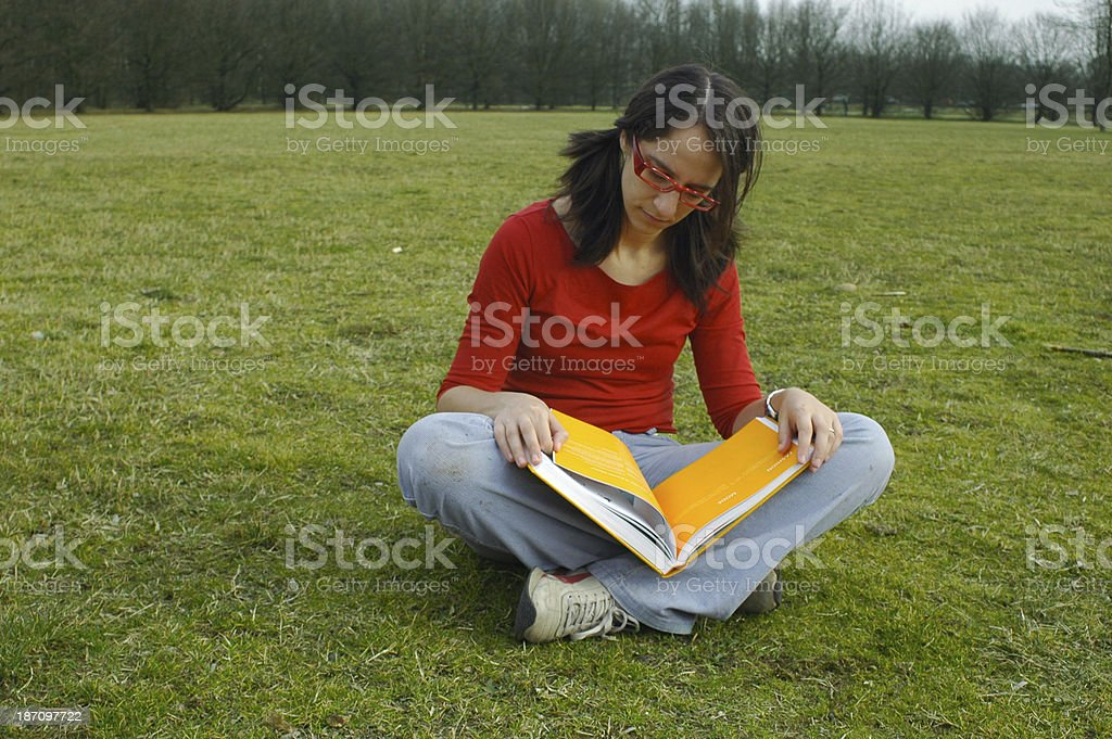 girl reading a book in the green grass stock photo