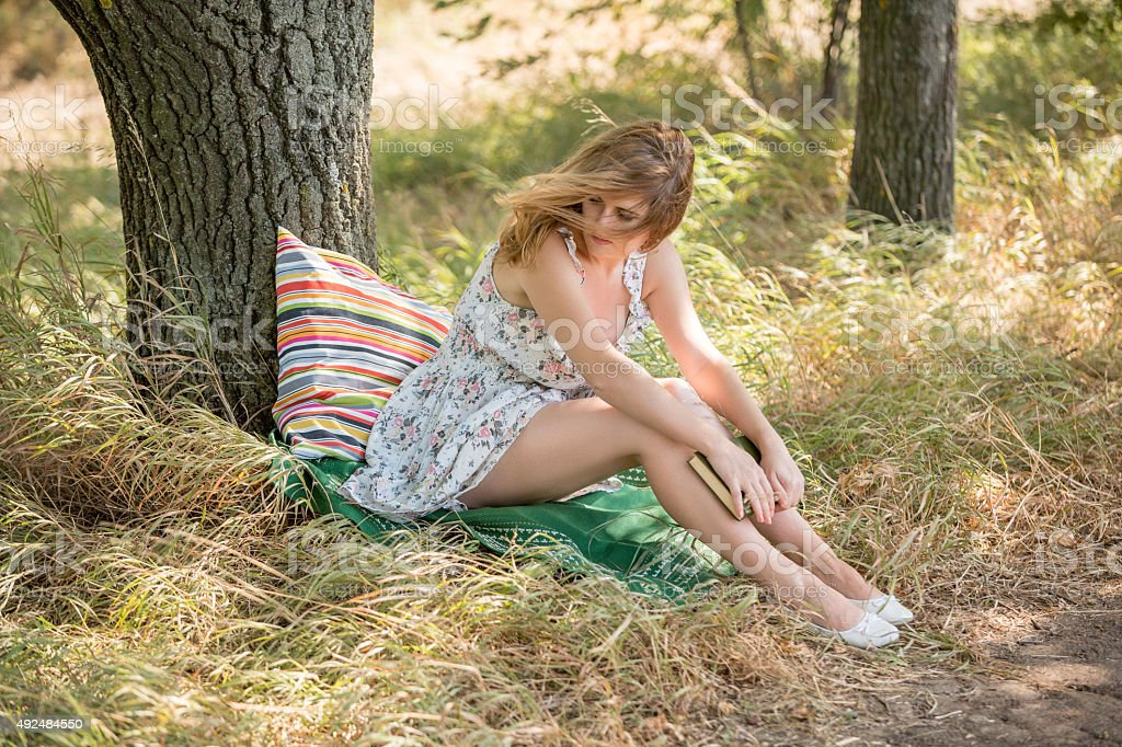 Girl reading a book in the park. stock photo